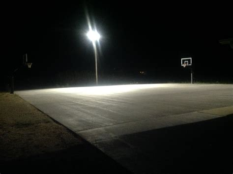 basketball courts with lights there are lights installed beside the court in the middle