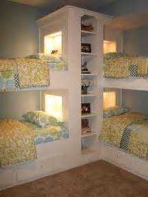 Corner bunk beds with lighted headboards and a bookshelf in between