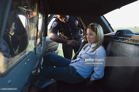 woman arrested handcuffed mid adult woman arrested by a police officer sitting in a