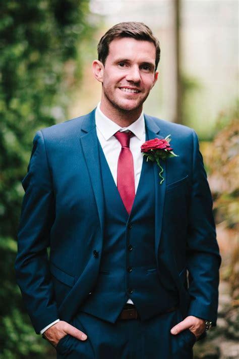 Groom in a navy suit with red tie {via weddingideasmag.com