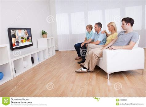 asian family watching tv together in living room this is family watching widescreen television stock photo image