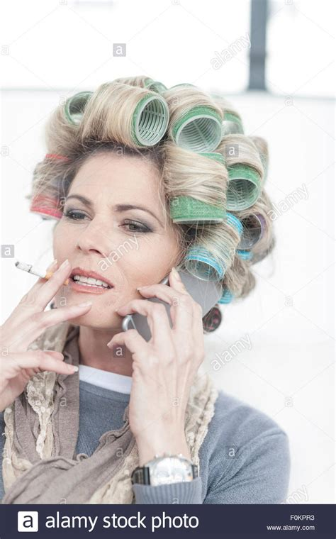 smoking in curlers portrait of woman with hair curlers smoking a cigarette