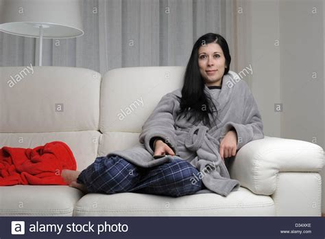 Young Woman Watching Tv At Home Sitting On A White Sofa
