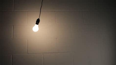 swinging light abstract swinging light bulb in dark room stock footage