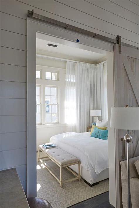 Beach Home Bedroom With Pecky Cypress Barn Door On Rails | beach home bedroom with pecky cypress barn door on rails