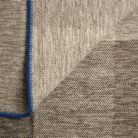 the woven wool phaedra hand woven wool throw with marine blue detail