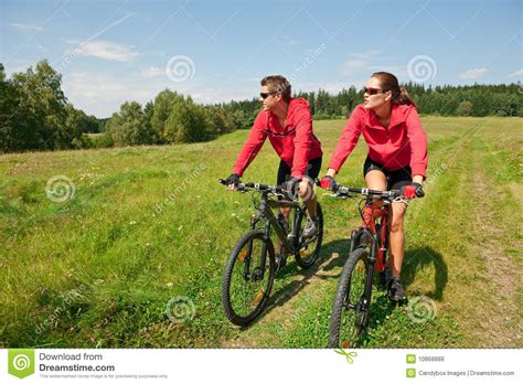 summer motorcycle riding summer sportive couple riding bike in meadow stock image
