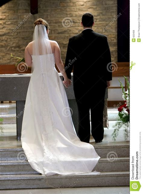 young couple holding hands  altar  wedding day stock
