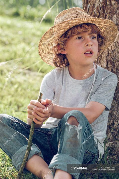 barefoot boy sitting  tree dreaming kid stock