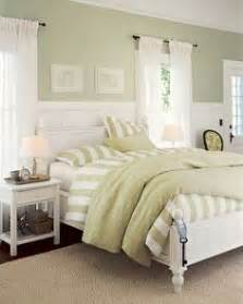 sage green accent wall behind the all white bed with sage green accent wall behind the all white bed with