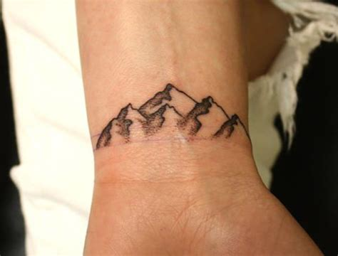 mountain wrist tattoo dotwork small mountains on wrist