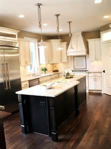 White Kitchen With Black Island Dark Wood Floors With Cream Cabinets And Dark Island