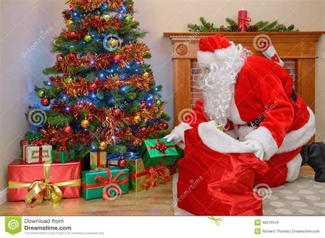 father christmas putting gifts under the tree stock photo