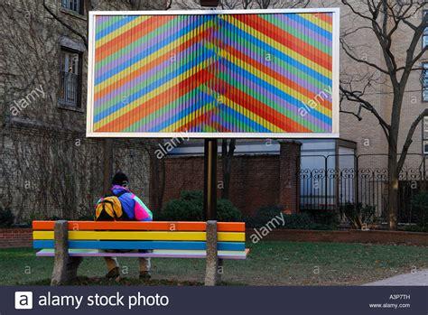 bench billboard man on bench watching billboard art installation in a city parkette stock photo