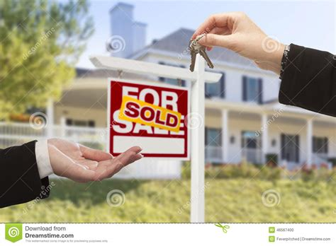 house and key real estate sold sign and agent handing over keys to new home stock