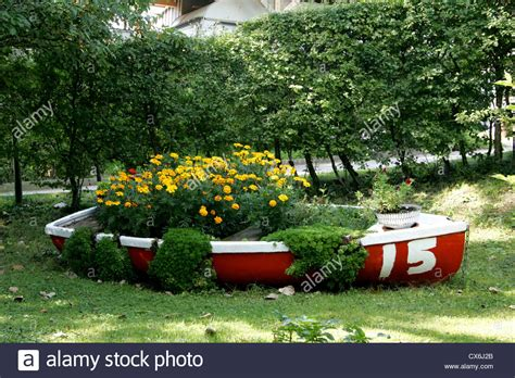 boat made into bed red rowing boat made into flower bed yellow flowers