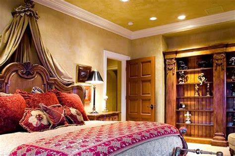 yellow paint color on the walls and ceiling in this tuscan style master bedroom which also