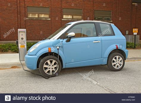 smart car charging station a light blue electric smart car being charged at a