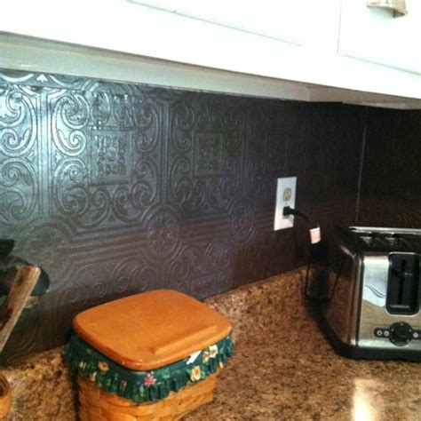 faux tin wallpaper painted with rubbed bronze spray paint