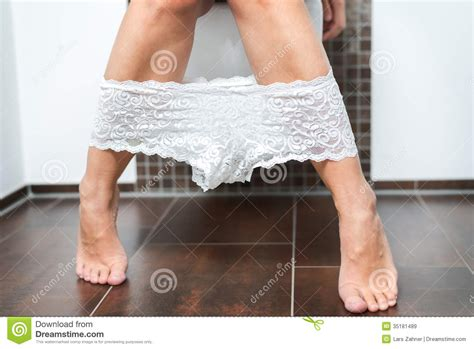 lying naked on the bathroom floor woman with her panties around her ankles royalty free