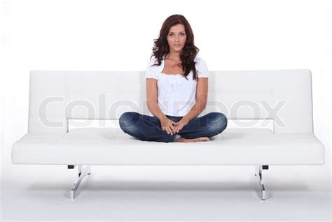 sitting in sofa woman sitting cross legged on a white sofa stock photo