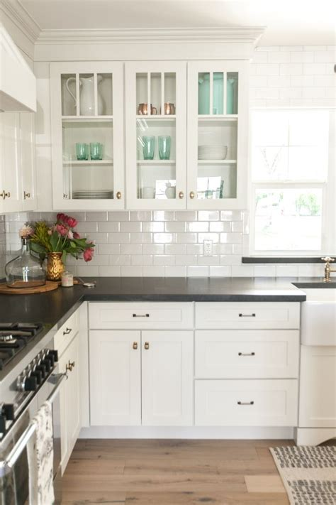 kitchen cabinets with glass on top white kitchen cabinets black countertops and white subway