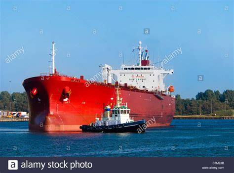 tugboat work a huge red oil tanker and a tugboat at work stock photo