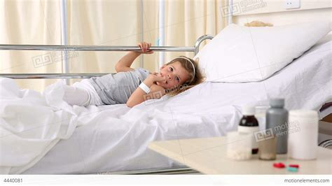 girl in hospital bed little girl lying in hospital bed looking at medic stock