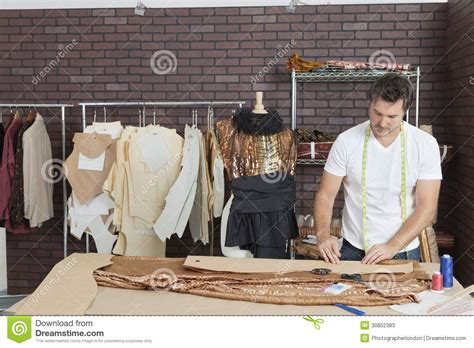 design fashion by using a fashion studio mature male fashion designer working in design studio