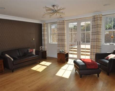 photo of simple brown leather living room with wood