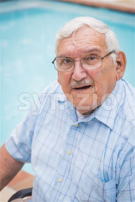 80 year old man short hair cuts old man with glasses sitting in deck chair stock photo