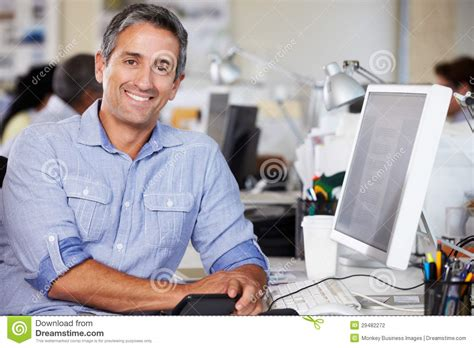 mens office desk man working at desk in busy creative office stock