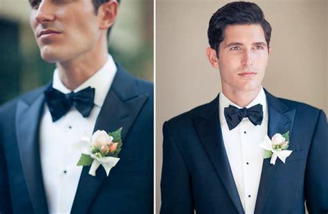daper groom wears navy tux and bow tie onewed com