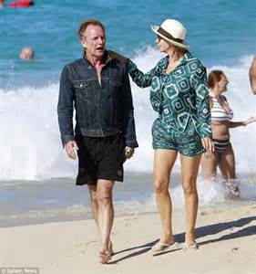 sting and trudie enjoy a romantic walk along the beach