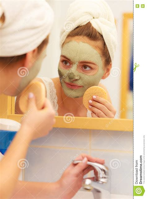 bathroom facial woman removing facial clay mud mask in bathroom royalty