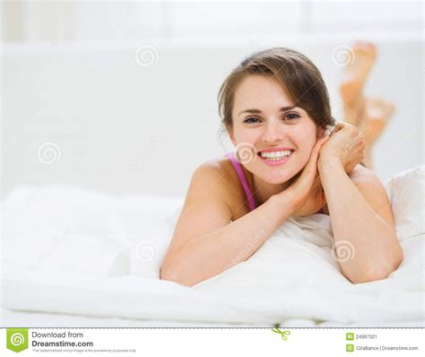 how to make a woman happy in bed happy woman laying in bed stock image image 24997321