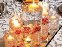 water with floating candle in vase with saran wrap or