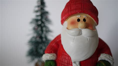 santa claus figurine with snowy tree in background no