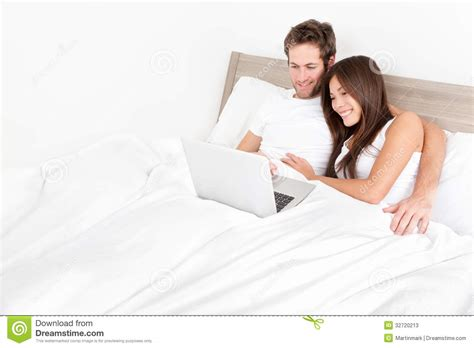 pictures couple in bedroom bed couple happy on laptop computer in bed room stock