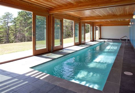 modern small pool house floor modern indoor pool design exposed wooden sloping rooftop concrete tiles floor wooden beam