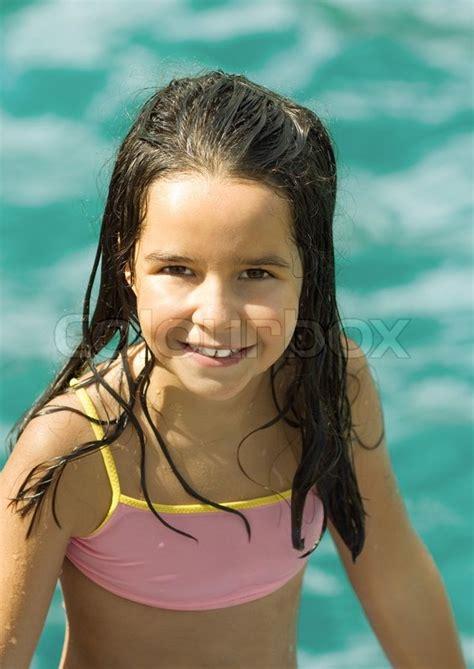 preteen swim girl in bathing suit water in background portrait