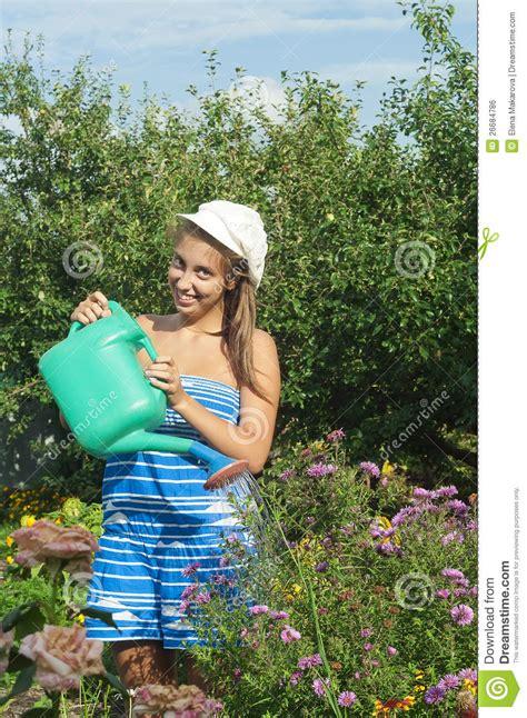 girl watering flowers girl is watering the flowers royalty free stock image