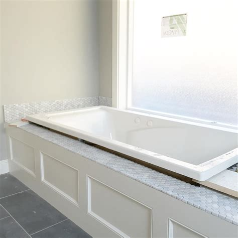 bathtub deck white jetted tub with carrara hexagon honeyb backsplash