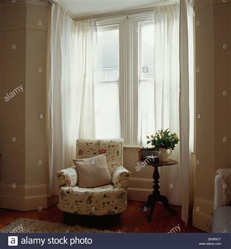 how to dress a window with voile and curtains patterned cream armchair in front of bay window with white