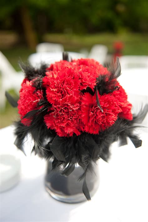 centerpiece with red carnations and black feathers