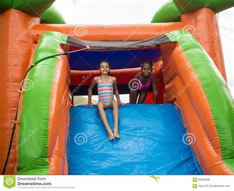 little girl house happy little girls sliding down an inflatable bounce house stock photo image 65562068