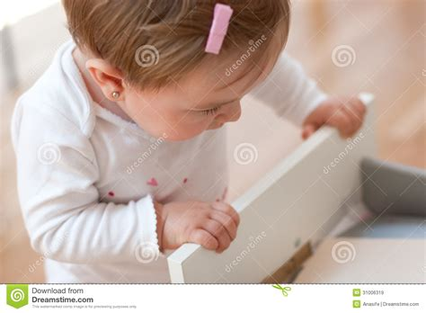 Baby In Drawer by Baby Looking Inside A Drawer Royalty Free Stock Images