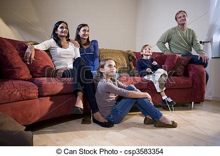 couch free tv stock photo of interracial family sitting on living room