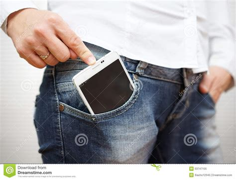 big mobile pushing big mobile phone in pocket stock photo