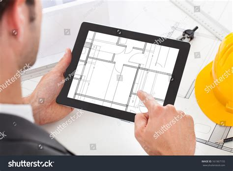 male architect with digital tablet studying plans in closeup male architect holding digital tablet stock photo